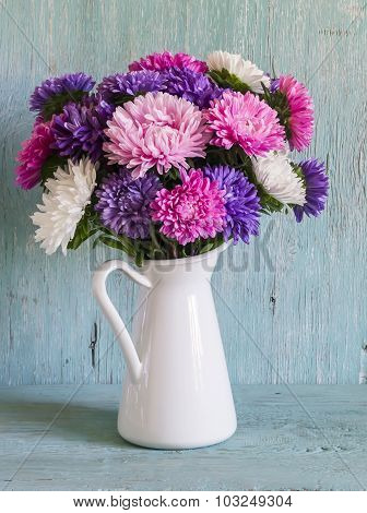 Flowers Asters In White Enameled  Pitcher On A Blue Wooden Surface