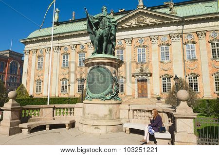 Lady relaxes at the bench in front of the House of Nobility, Stockholm, Sweden.