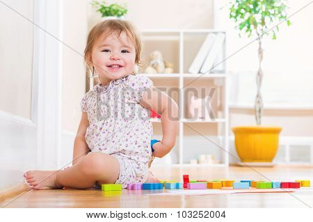 Toddler Girl Smiling While Playing With Wooden Toy Blocks