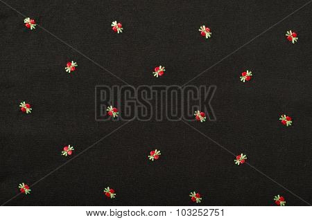 Small Red Floral Pattern On Black Fabric.