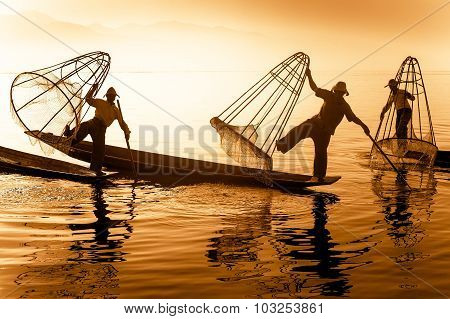 Burmese fisherman on bamboo boat catching fish. Inle lake Myanmar