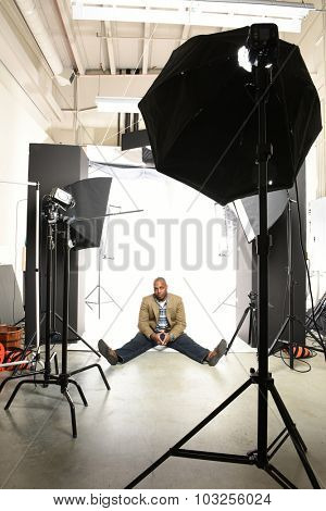 Young African American businessman sitting on floor of photo studio