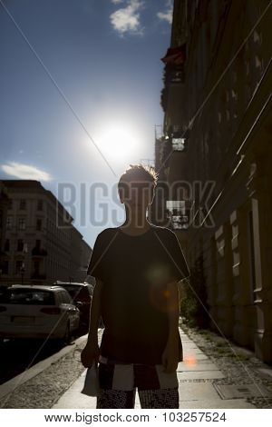 Backlit Shot Of A Boy On A Street