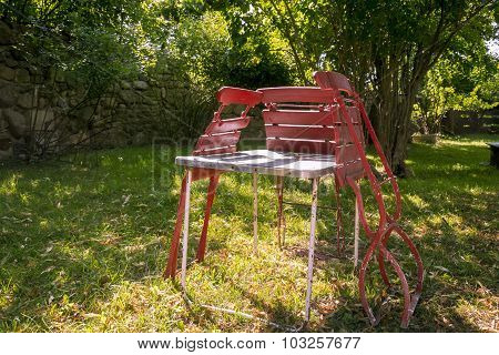 Three Old, Red Folding Chairs Leaning Against A Table