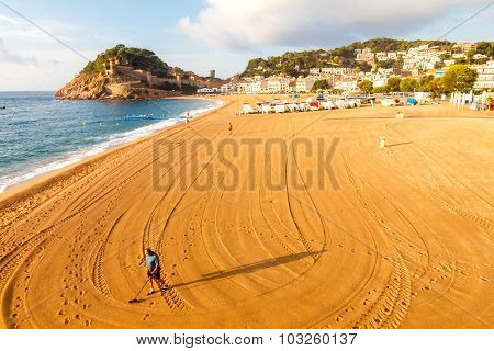 Man with metal detector on the beach of Tossa de Mar.