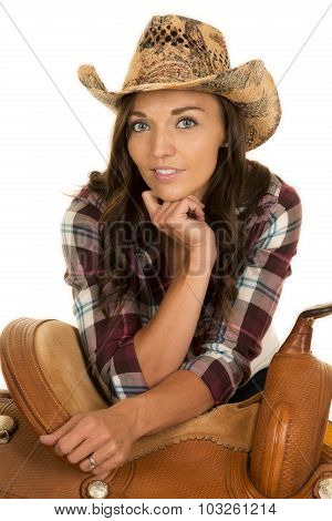Cowgirl In Plaid Shirt And Hat Lean On Saddle Looking