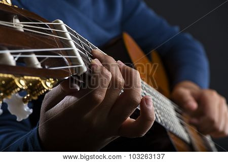 Close up of child playing classical guitar.