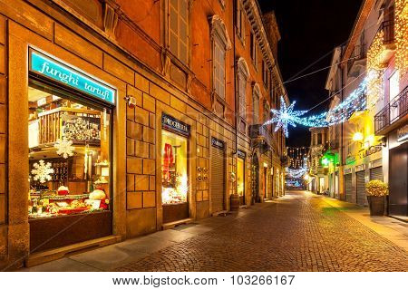 ALBA, ITALY - DECEMBER 07, 2011: Pedestrian street and shops in old town illuminated for Christmas celebrations. This area is very popular with locals and tourists visiting Alba for winter holidays.