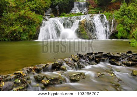 Nice waterfall's cascade on river in autumn forest