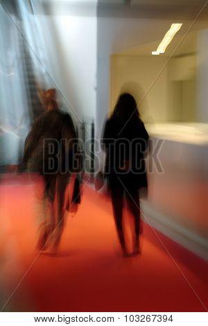 two people walking indoor in a corridor