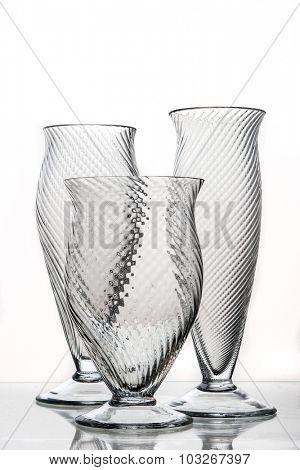 three decorative glasses on a mirrored desk