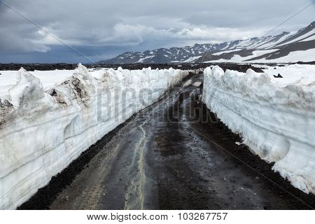 Dirt road in Iceland with snow walls