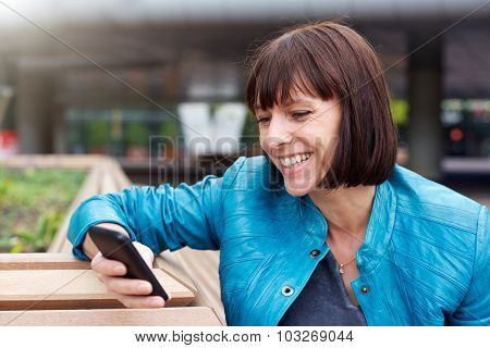 Mature Woman Smiling And Looking At Cell Phone