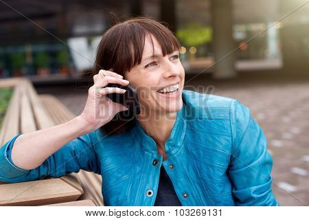 Woman Smiling And Listening To Mobile Phone