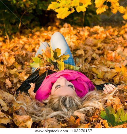 Image Of A Youngl Girl Lying In Autumn Leaves