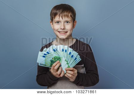 Boy teenager European appearance ten years  holding a wad of mo