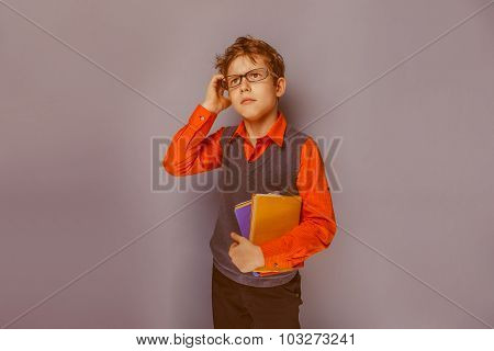 European-looking boy  of ten years  in glasses  thinking  intent