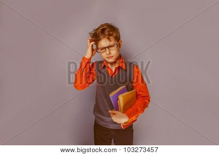European-looking boy  of ten years  in glasses thinking intently