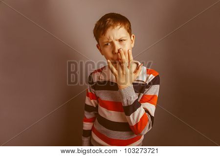 European-looking boy of ten years licks his finger on a gray bac