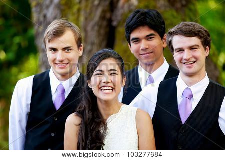 Bride Standing With Her Three Groomsmen Outdoors Under Large Tree