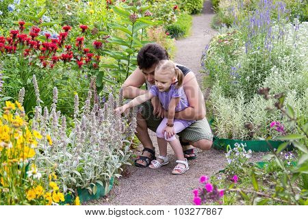 Dad With His Little Daughter Looking At Flowers In The Park