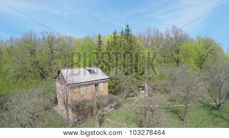 Country house among plants near forest at spring sunny day. Aerial view video frame