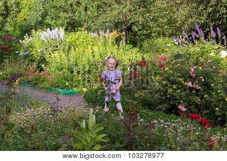 Cheerful Little Girl Among Flowers In Park