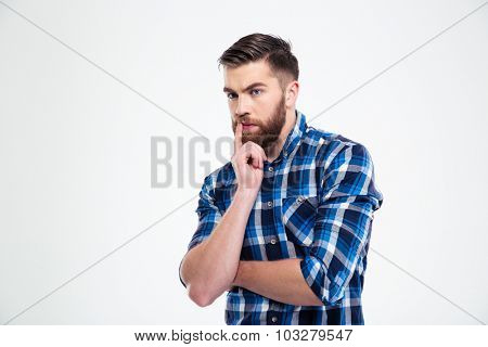 Portrait of a young casual man thinking isolated on a white background