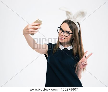 Portrait of a smiling girl with bunny ears making selfie photo on smartphone isolated on a white background