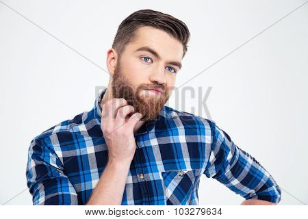 Portrait of a a pensive man touching his beard with hand isolated on a white background