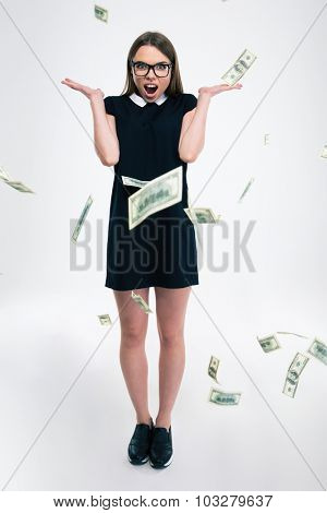 Full length portrait of a cheerful girl standing under rain with dollar bills isolated on a white background