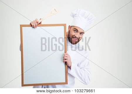 Portrait of a happy male chef cook holding blank board isolated on a white background