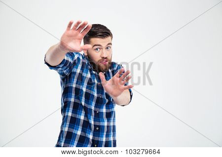 Portrait of a handsome man showing stop gesture with palms isolated on a white background