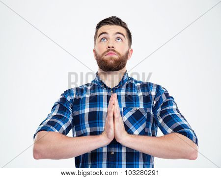 Portrait of a casual man praying isolated on a white background