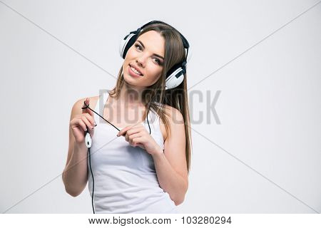 Portrait of a happy charming girl listening the music in headphones isolated on a white background