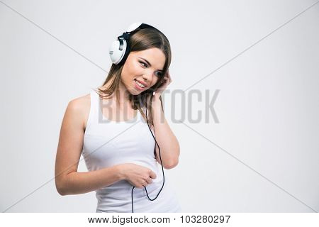 Portrait of a happy girl listening the music in headphones isolated on a white background