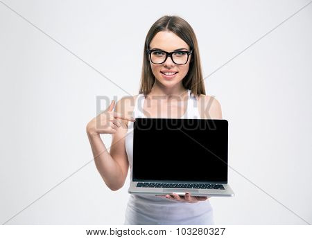 Portrait of a smiling girl pointing finger on a blank laptop screen isolated on a white background