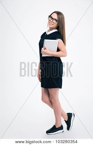 Full length portrait of a smiling young woman standing with tablet computer isolated on a white background