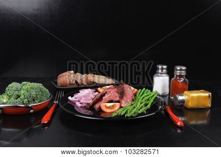 business lunch fresh roast beef meat slices on black plate with cutlery asparagus boiled broccoli rye bun on wooden table
