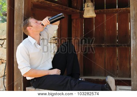 young happy white Caucasian man taste and enjoy red wine outdoor in in countryside . classic style fashion.