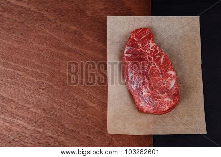 fresh raw beef rib eye steak on black walnut wooden table