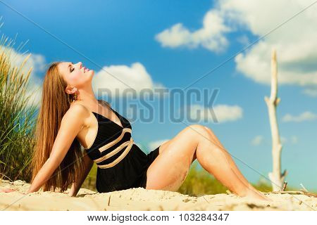 Woman Sunbathing On Beach.