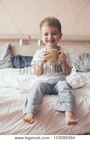 2 years old little body dressed in pajamas are relaxing and drinking milk in the bed, warm and cozy scene. Pastel colors, selective focus.