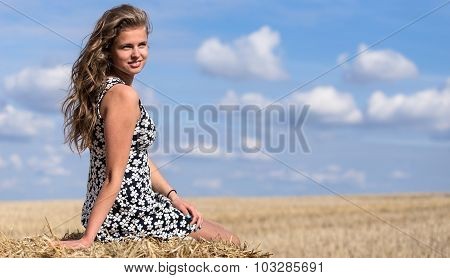 Full length portrait of young adult girl on haystack against blue sky with clouds and autumn field