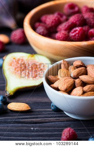 Bowl with berries and nuts over dark wooden background. Health and diet concept.