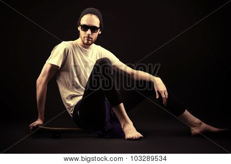 Young man in hat sitting on his skateboard over black background.