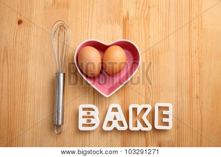 baking concept hand whisk next to eggs in a heart shape container