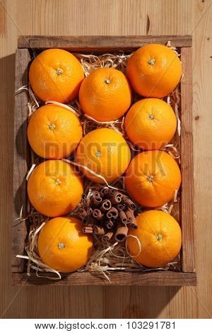 oranges  and cinnamon stick on old wooden crate. Top view