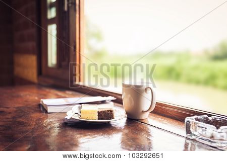 Cake And Cup Of Coffee On Wooden Table Near Window Sill. Time With Snacks Concept.