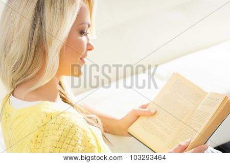 Beautiful smiling excited woman reading a book in the morning.